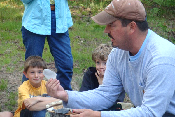 Eric Drake, USFS archaeologist, demonstrates flint knapping, on Grand Island.