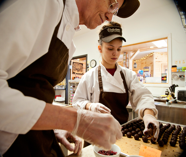 Livia Worley, 20, right, helps Dale Anderson coat truffles in chocolate at Confections with Convictions.