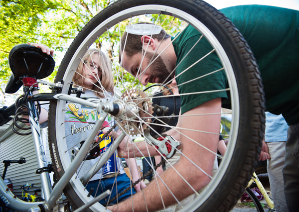 James Clemons, 14, learns to clean and oil a chain with Open Roads volunteer Sean Walker.