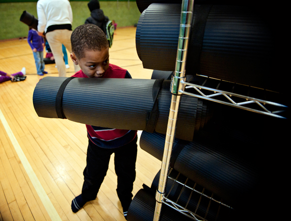 A young student puts his yoga mat back as part of The Developing the Community School Project.
